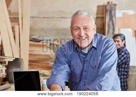 Smiling senior citizen as carpenter in carpentry shop