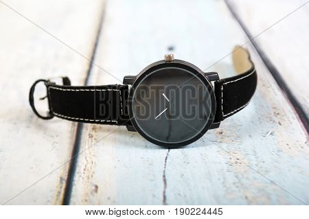 Black watch on black thong is isolated on a wooden background