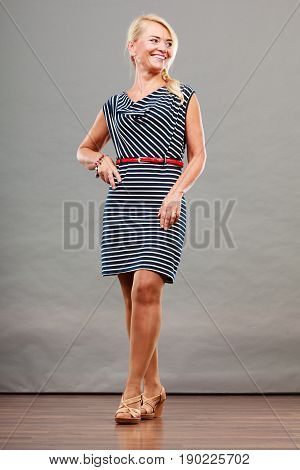 Mid adult blond attractive woman in full length wearing striped dress sandals shoes posing studio shot on gray