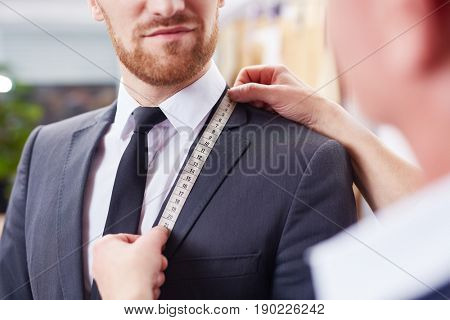 Closeup image of tailor taking measurements of jacket to fit bespoke business suit