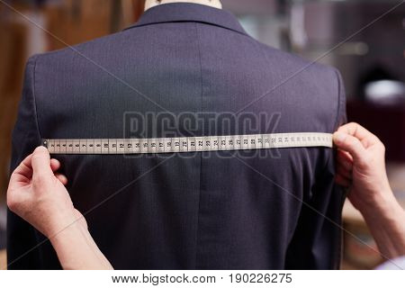 Closeup of tailors hands measuring back of jacket with tape fitting custom suit