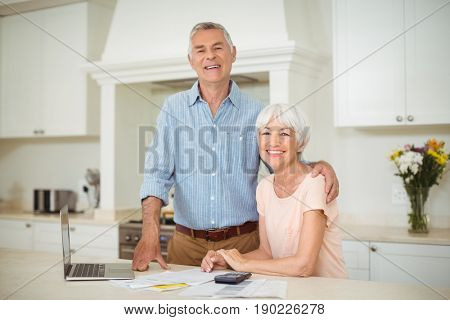 Senior man interacting with senior woman in kitchen at home