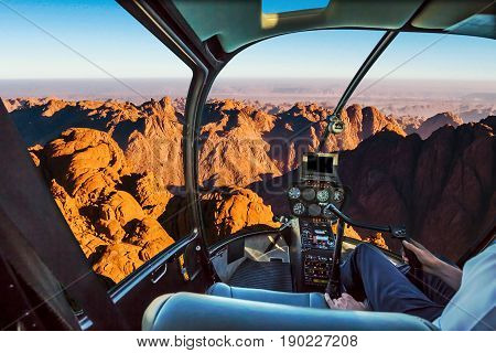 Helicopter cockpit flight aerial view of the holy summit of Mount Sinai, Aka Jebel Musa, 2285 meters, at sunrise, Sinai Peninsula in Egypt. Spirituality, religion and history concept.