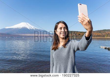 Woman taking selfie with cellphone in Fujisan