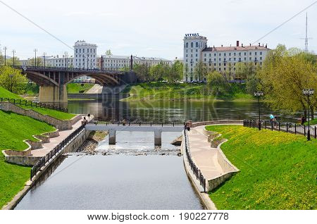 VITEBSK BELARUS - MAY 15 2017: Beautiful May view of estuary of river Vitba and Kirovsky bridge across Western Dvina. Unknown people walk along waterfront Vitebsk Belarus
