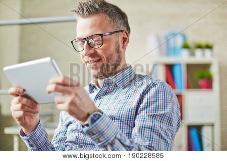 Positive middle-aged entrepreneur in eyeglasses immersed in watching business webinar on tablet to develop own business