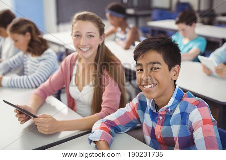 Portrait of students with digital tablet in classroom at school