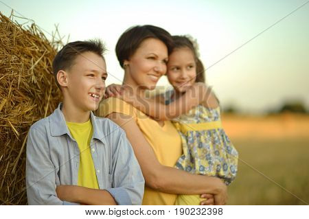 Mother with children standing near stack of hay