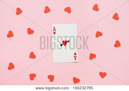 Heart Ace Of Playing Card With Red Hearts Lying Around On Pink Surface