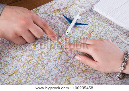 Couple planning vacation trip to Europe, closeup of fingers point to Vienna on map
