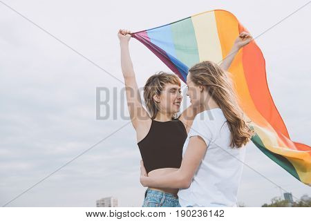 Smiling Young Homosexual Couple Holding Lgbt Flag And Hugging Outdoors