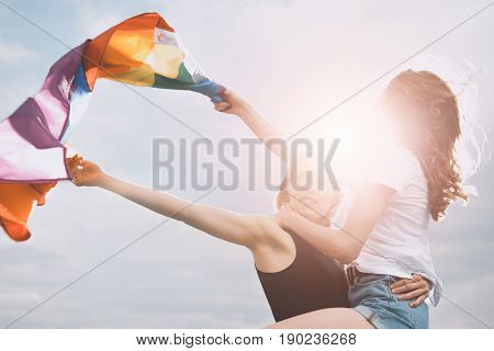 Young Homosexual Couple Holding Lgbt Flag And Hugging Outdoors
