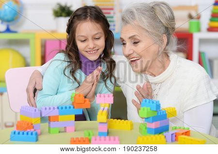 Portrait of a grandmother playing with her little granddaughter