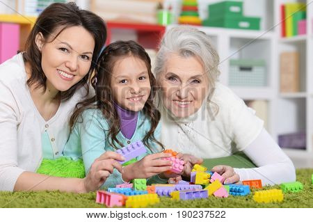 Little girl playing with mother and grandmother