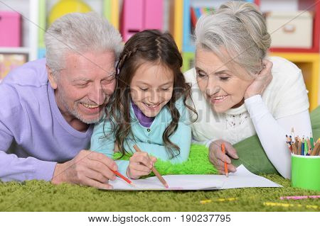 Little girl with grandparents lying on floor and drawing picture