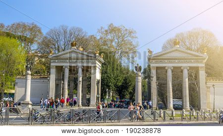 Rome Italy aprile 2017: Tourists walking by the Monumental entrance of Villa Borghese in Rome viewed from Piazza del Popolo