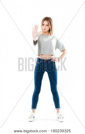 Full length portrait of a serious pretty girl standing showing stop gesture with hand isolated over white background