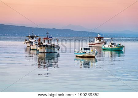 Traditional wooden fishing boats at sunset in Peloponnese, Greece
