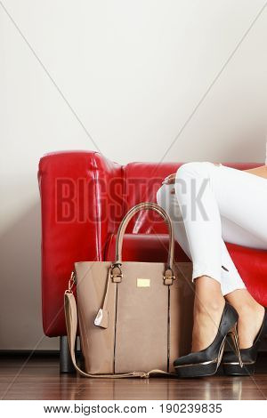 Woman Sitting On Sofa Presenting Leather Bag