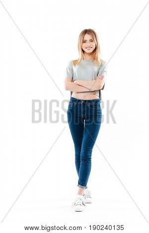 Full length portrait of a casual young girl standing with hands folded isolated over white background