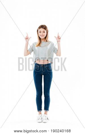 Full length portrait of a cheerful cute girl standing and pointing fingers up at copy space isolated over white background