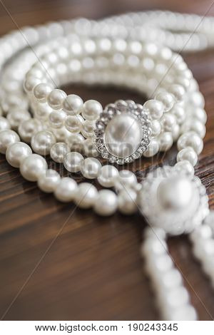 A pearl necklace and bracelet with a large pearl surrounded by diamonds lie on a dark brown wooden background
