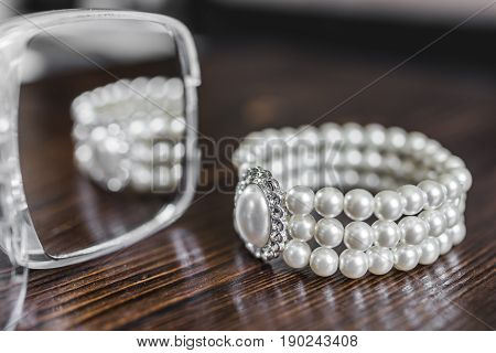 A bracelet made of white pearls with a large pearl surrounded by diamonds is reflected in the mirror and lies on a dark brown wooden background.