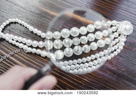 Pearl necklace with a large white pearl surrounded by diamonds under a magnifying glass on a dark brown background.
