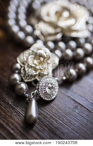 A necklace of black pearls with a large stone lies around a silver brooch in the form of a flower on a dark brown wooden background.