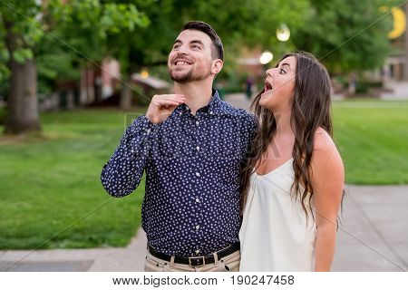 Two college students being funny for the camera during their graduation photos on campus at a university.
