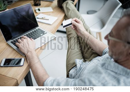 Senior Businessman Working On Laptop, Making Buying In Internet With Credit Card At Office