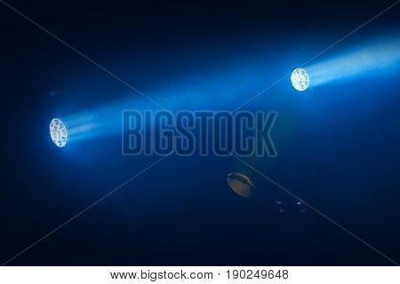 Blue Spot Lights With Rays In Smoky Dark