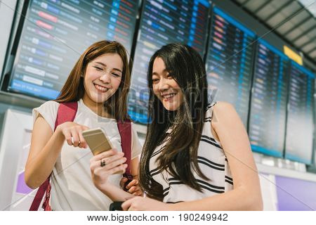 Two Asian girls using smartphone together at flight information board in airport. Online check-in timetable application or holiday travel concept