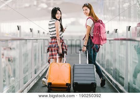 Two happy Asian girls traveling abroad together carrying suitcase luggage in airport. Air travel or holiday vacation concept