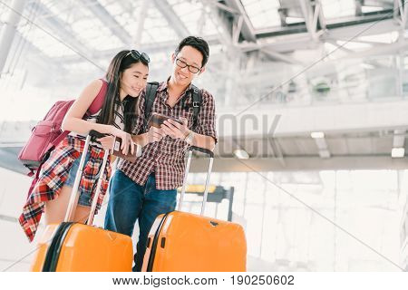 Asian couple travelers using smartphone checking flight or online check-in at airport with passport and luggage. Air travel or mobile phone technology concept