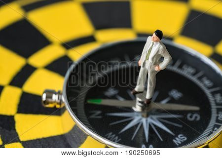 Miniature figure business man standing on compass in the center of dartboard as financial business success direction concept.