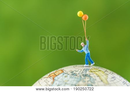 miniature child figure holding balloons standing on the globe world map with green background and copy space as travel or happy environment concept.