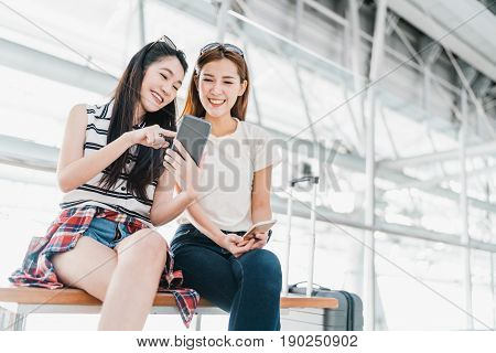 Two happy Asian girls using smartphone checking flight or online check-in at airport together with luggage. Air travel summer holiday or mobile phone application technology concept