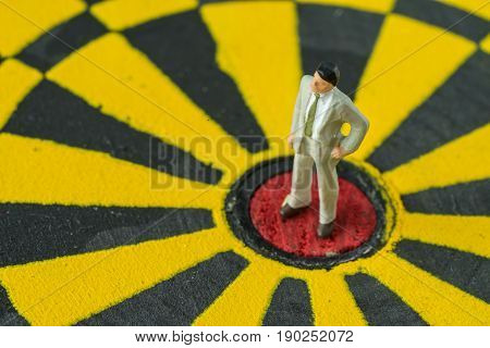 Miniature figure business man standing in the center of dartboard as business success concept.