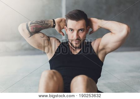 Man making exercise, sit-ups, crunches for abs muscles, training indoors