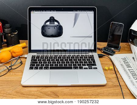 PARIS FRANCE - JUNE 6 2017: Apple Computers website on MacBook Retina in creative environment showcasing latest macOS High Sierra from Apple at WWDC 2017 - HTC vive vr headset with new iMAc