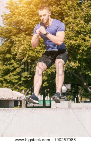 Fit fitness man doing exercises outdoors at park. The man doing hamstring leg exercises. The male sports model jumping outdoor in summer.