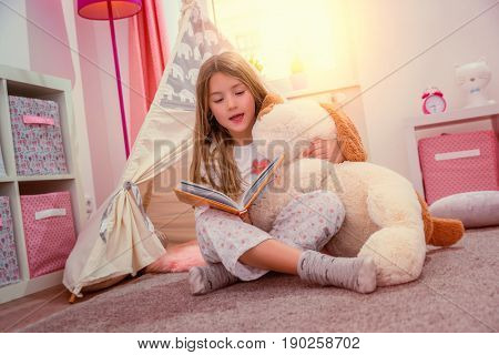 little cute girl reading book in her room