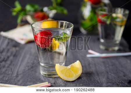 Flavored Water With Fresh Strawberries And Mint In Glass On A Black Wooden Table With Bright Details