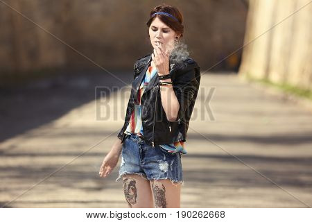 Beautiful young woman smoking weed outdoors