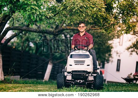 Gardening Details - Male Worker Using Motorised Tractor For Lawn Mowing.