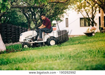 Man Working In Garden, Relaxing Day In Weekend And Cutting Grass With Lawn Mower