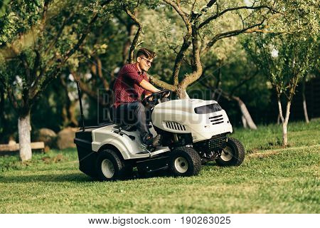 Portrait Of Handsome Man Working With Lawnmower And Driving In Garden
