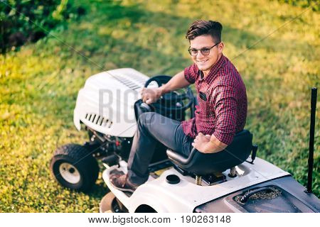 Portrait Of Male Using Industrial Lawn Mower And Cutting Grass