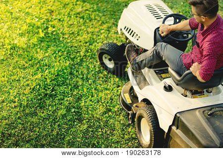 Top View Of Man Using Lawn Mower For Cutting Grass, Portrait Of Healthy Lifestyle And Weekends